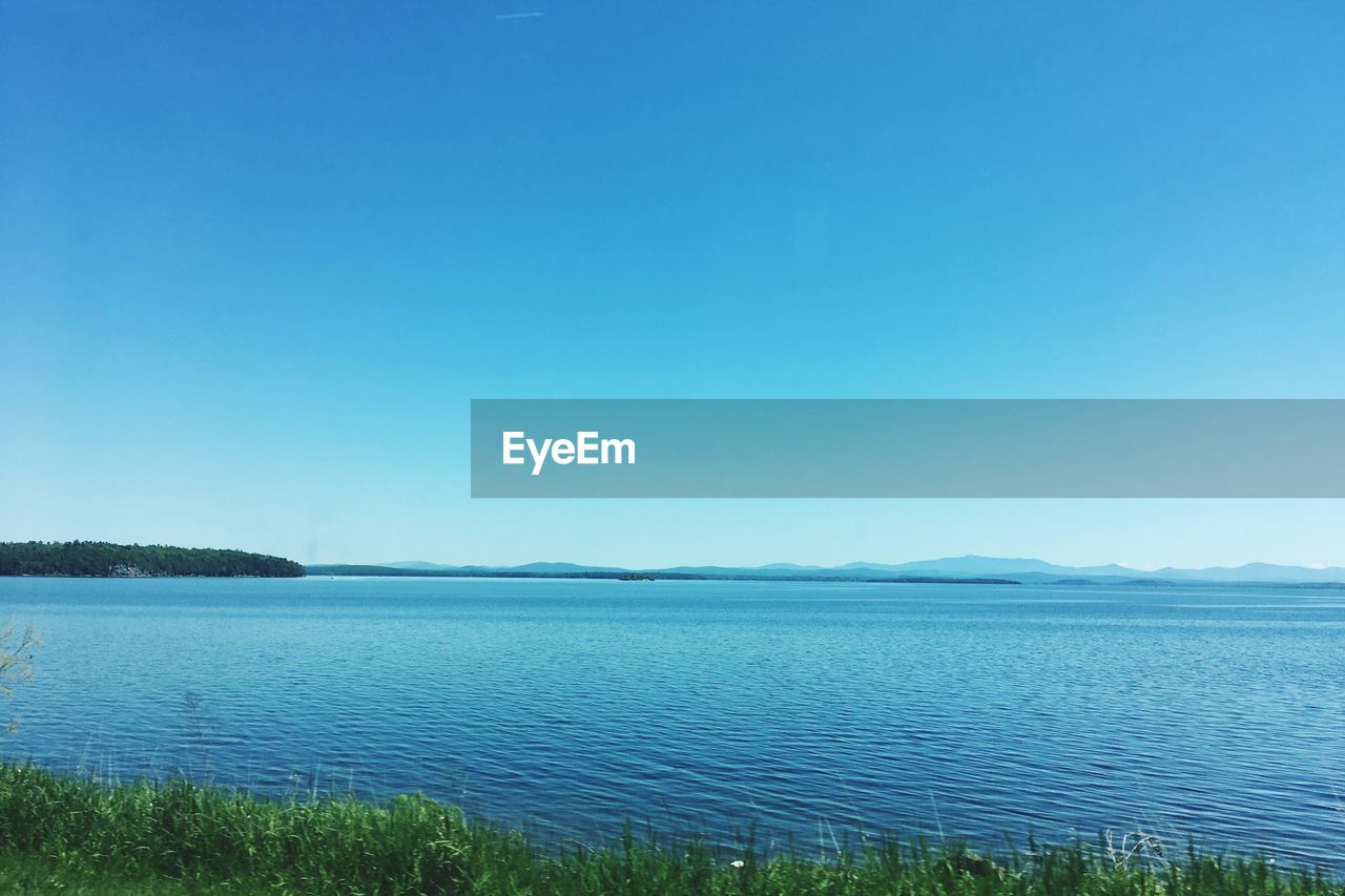 tranquil scene, water, tranquility, blue, nature, beauty in nature, scenics, outdoors, lake, copy space, no people, day, clear sky, grass, landscape, view into land, sky