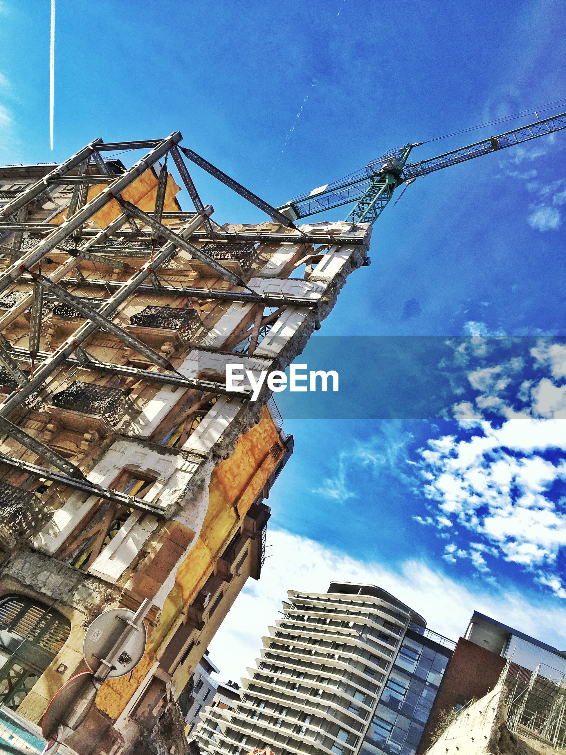 Low angle view of building under construction in city against sky