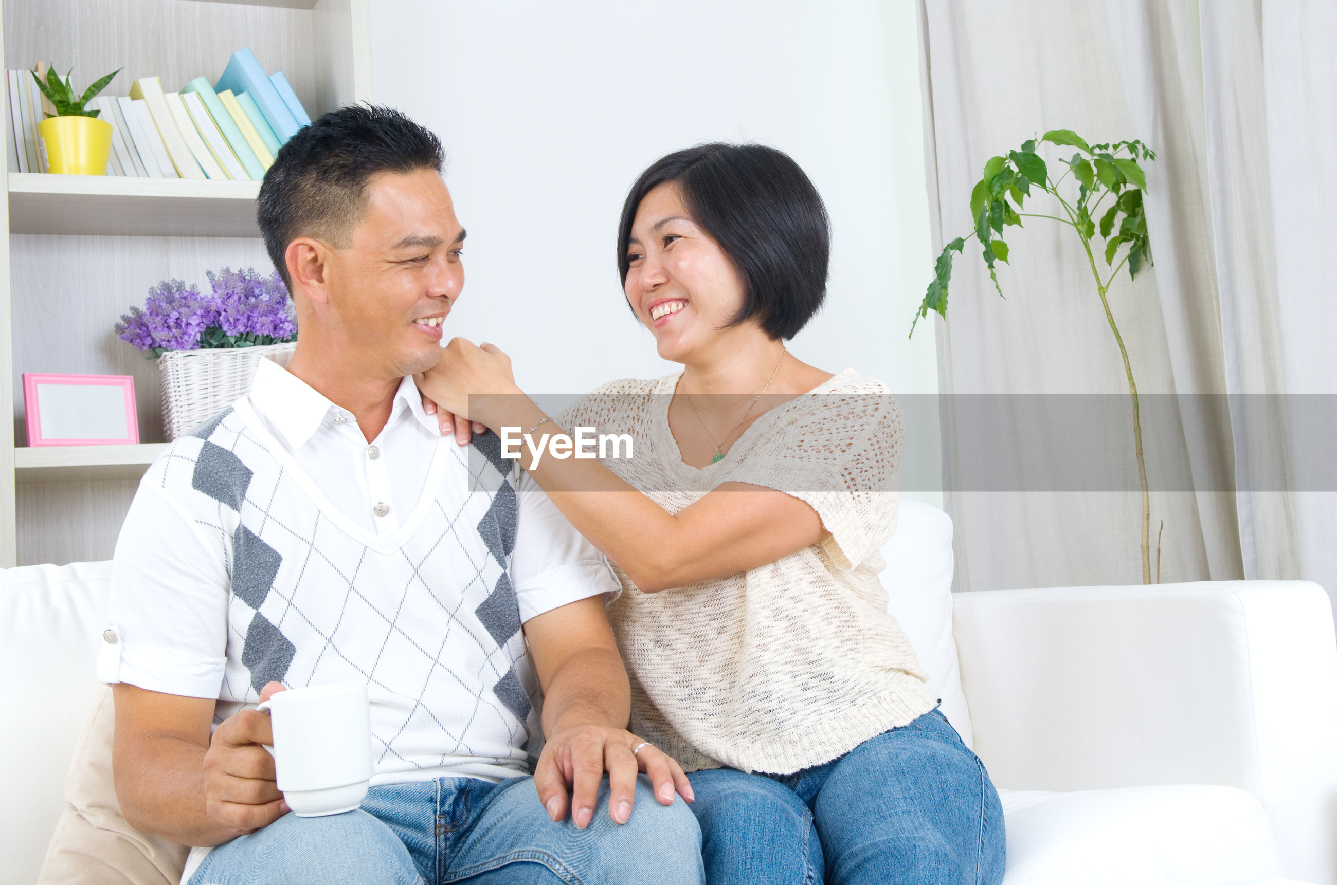 Smiling couple talking while sitting at home