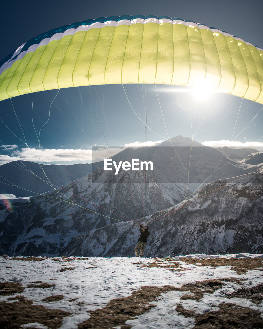 adventure, mountain, extreme sports, parachute, day, outdoors, sunlight, leisure activity, transportation, real people, sky, nature, flying, snow, beauty in nature, hot air balloon, one person, paragliding, people