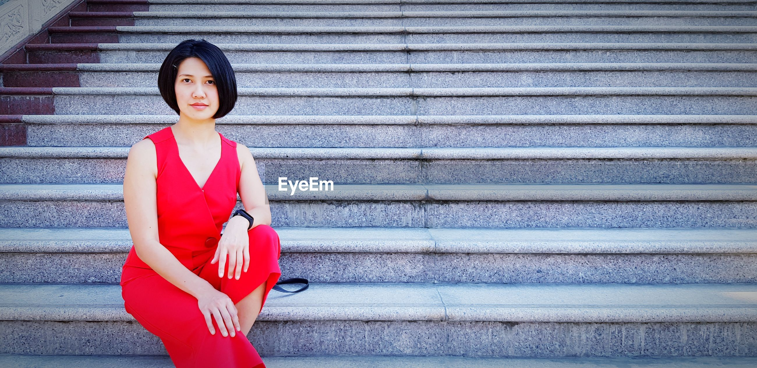 Asian woman in red dress sitting on staircase
