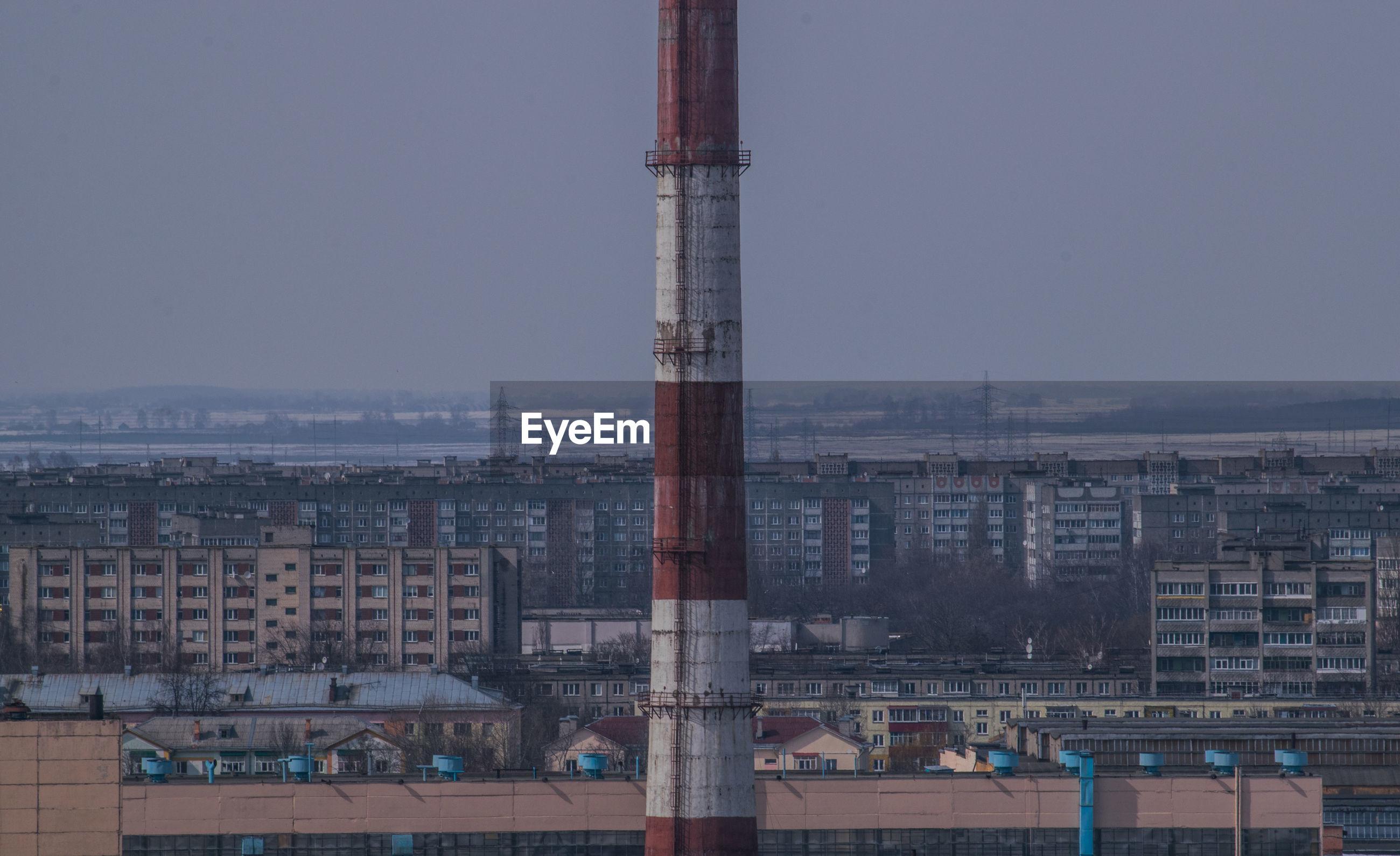 Tower amidst buildings against clear sky