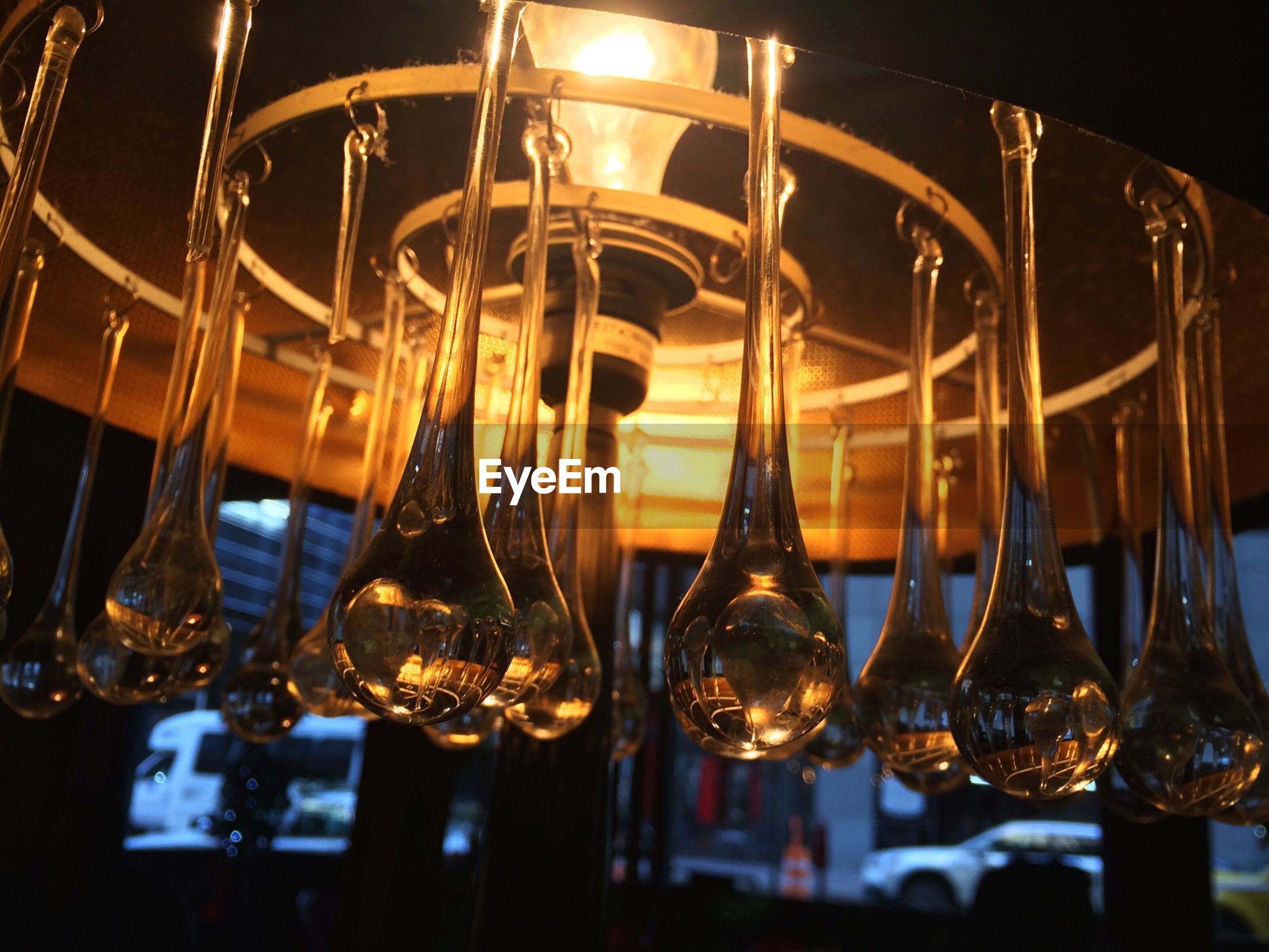 Low angle view of illuminated light bulb amidst glass decorations at cafe