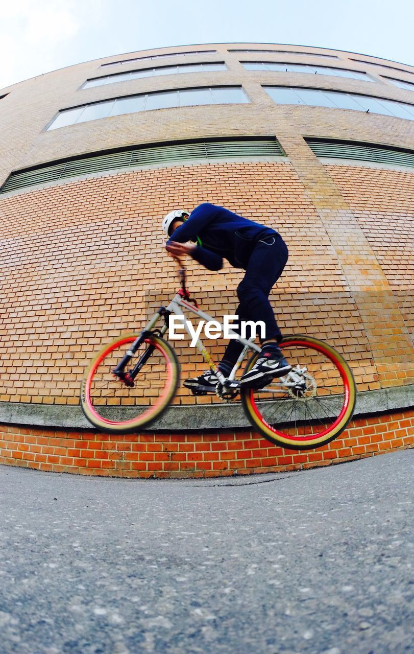 bicycle, full length, transportation, cycling, mode of transport, leisure activity, helmet, outdoors, stunt, day, bmx cycling, real people, one person, lifestyles, balance, motion, side view, headwear, men, risk, sport, skill, sports helmet, exercising, land vehicle, activity, cycling helmet, sky, sportsman, young adult, adult, people