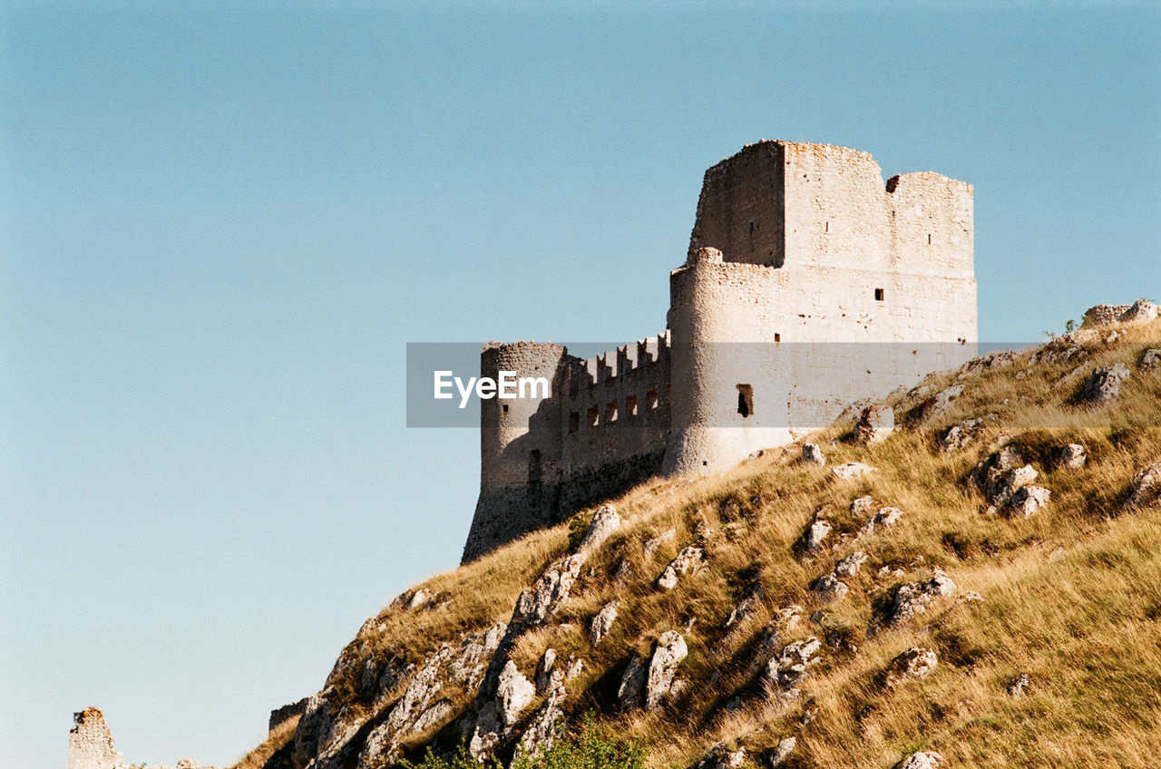 architecture, building exterior, history, built structure, fort, castle, copy space, clear sky, the past, day, low angle view, ancient, no people, travel destinations, past, outdoors, sky, nature, ancient civilization