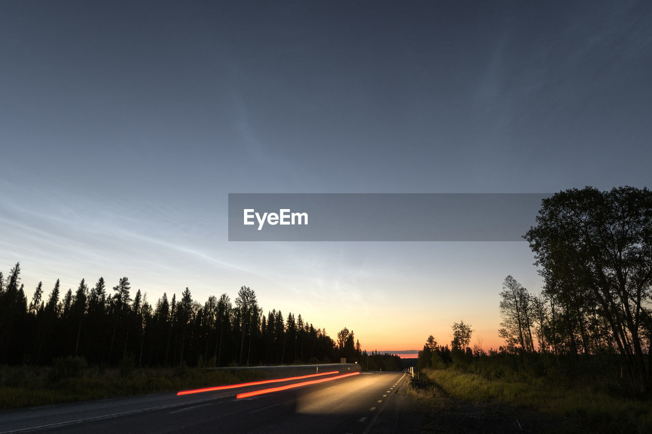 tree, sky, road, plant, transportation, nature, sunset, the way forward, beauty in nature, direction, no people, scenics - nature, road marking, marking, symbol, cloud - sky, tranquility, sign, non-urban scene, outdoors