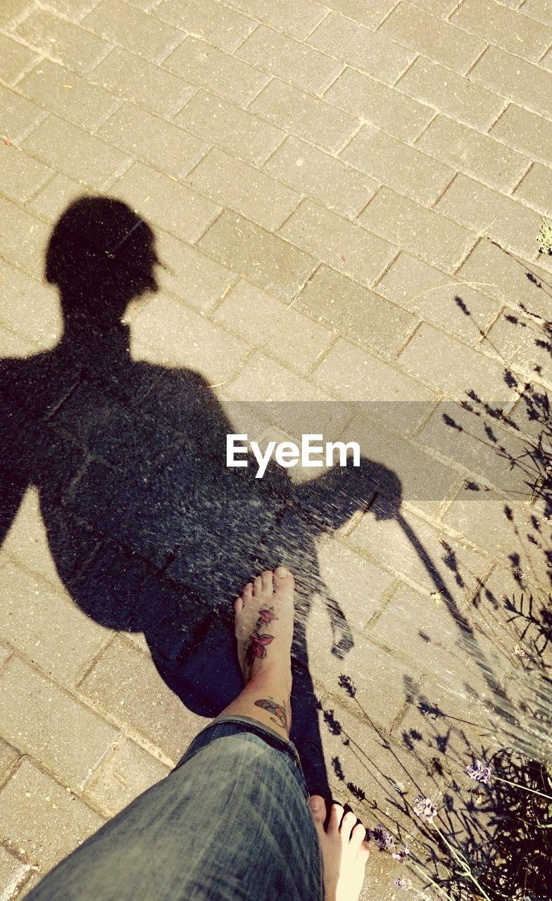 Shadow Of Woman Walking On Walkway