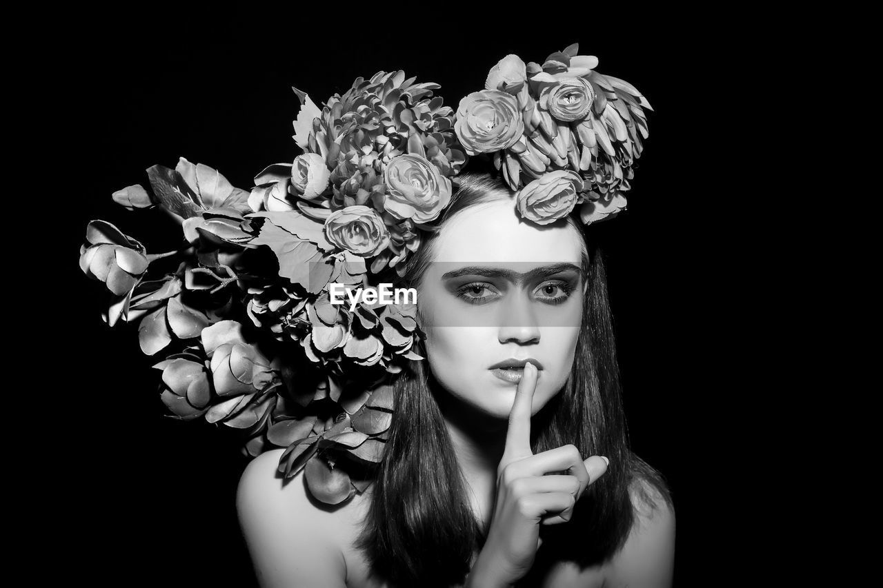 Portrait of fashion model wearing flowers with finger on lips against black background