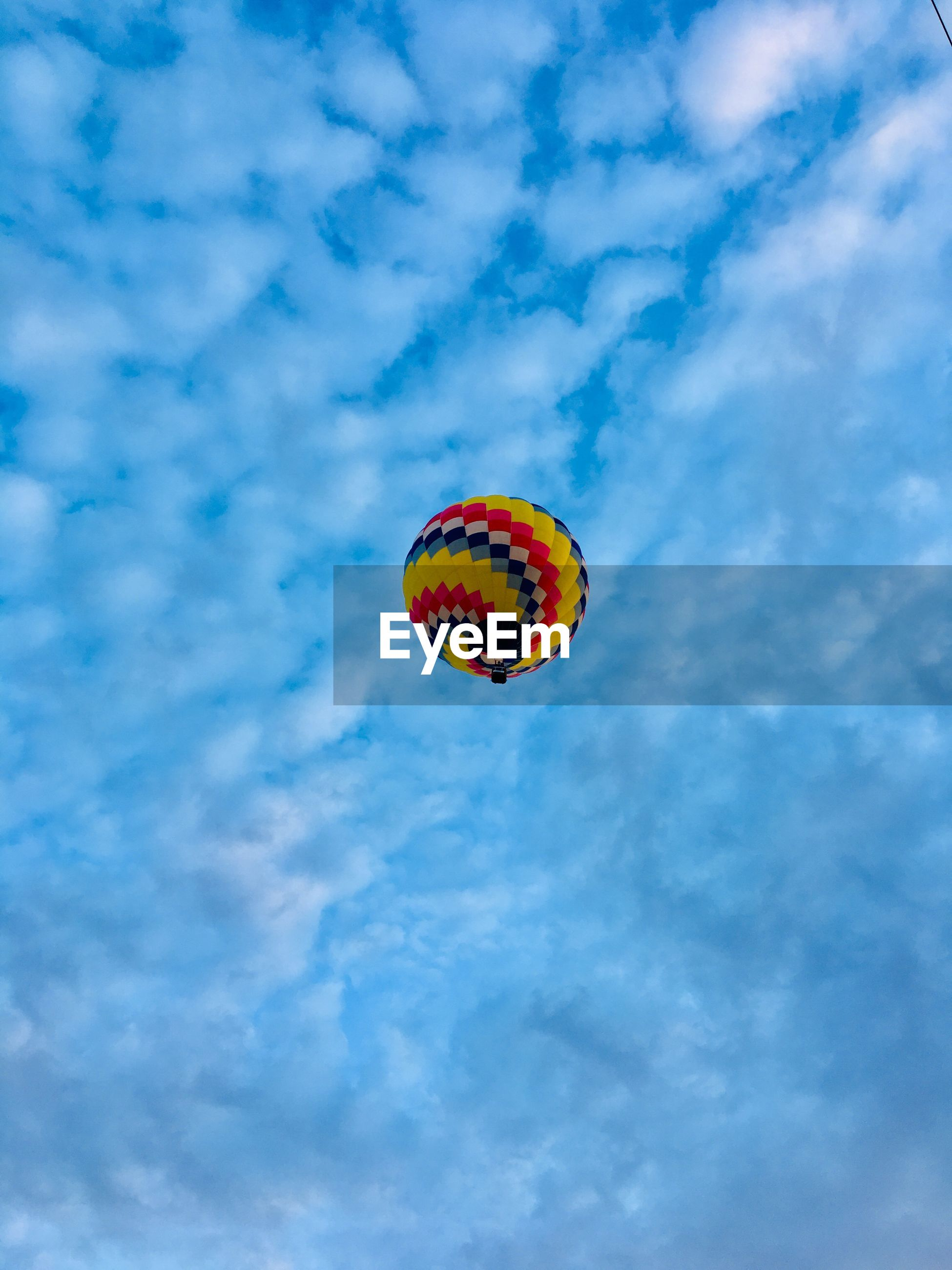 sky, cloud - sky, low angle view, mid-air, nature, blue, adventure, day, flying, sport, extreme sports, multi colored, outdoors, no people, freedom, parachute, beauty in nature, transportation, balloon, orange color