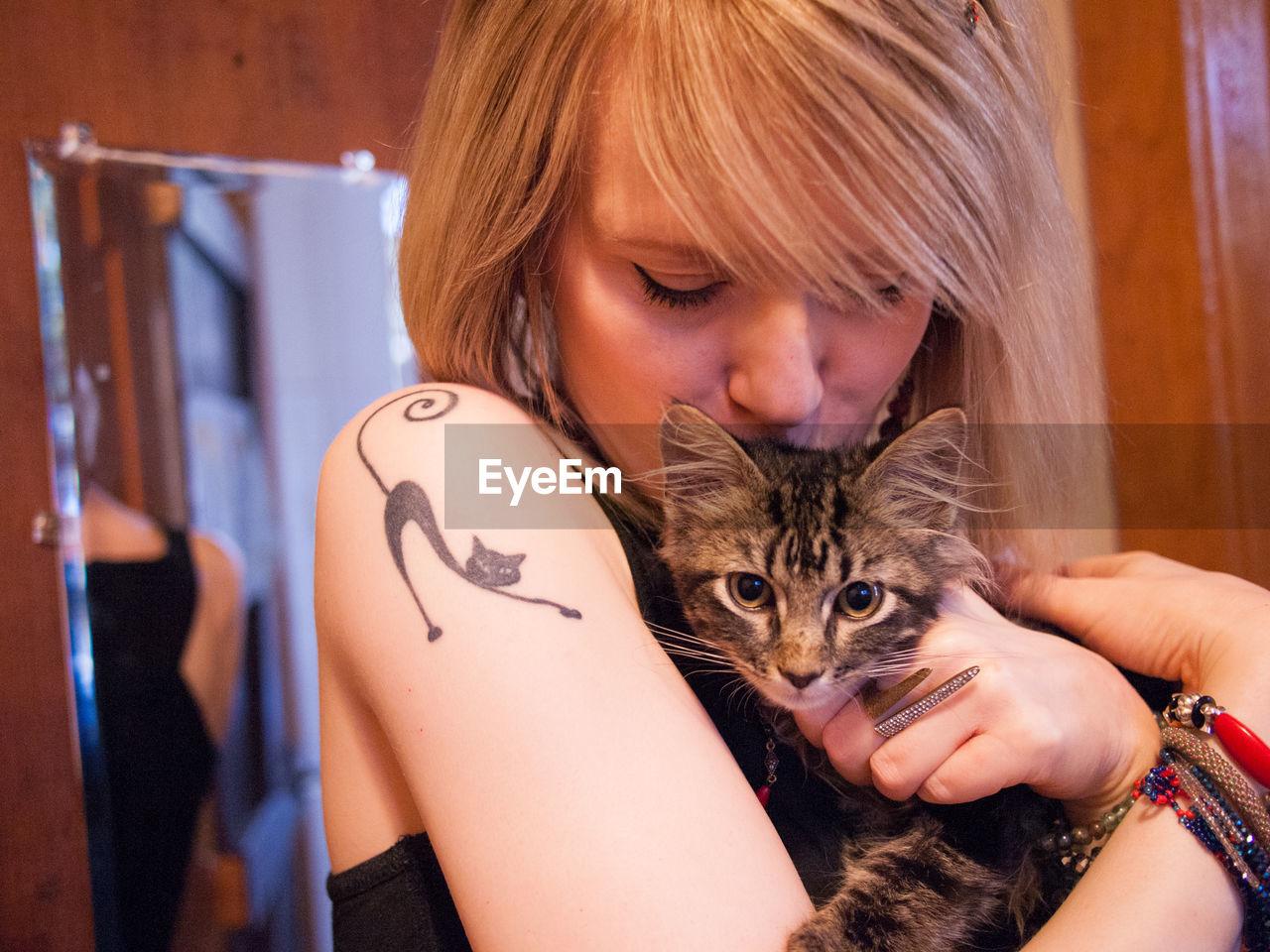 Close-Up Of Woman Kissing Cat At Home