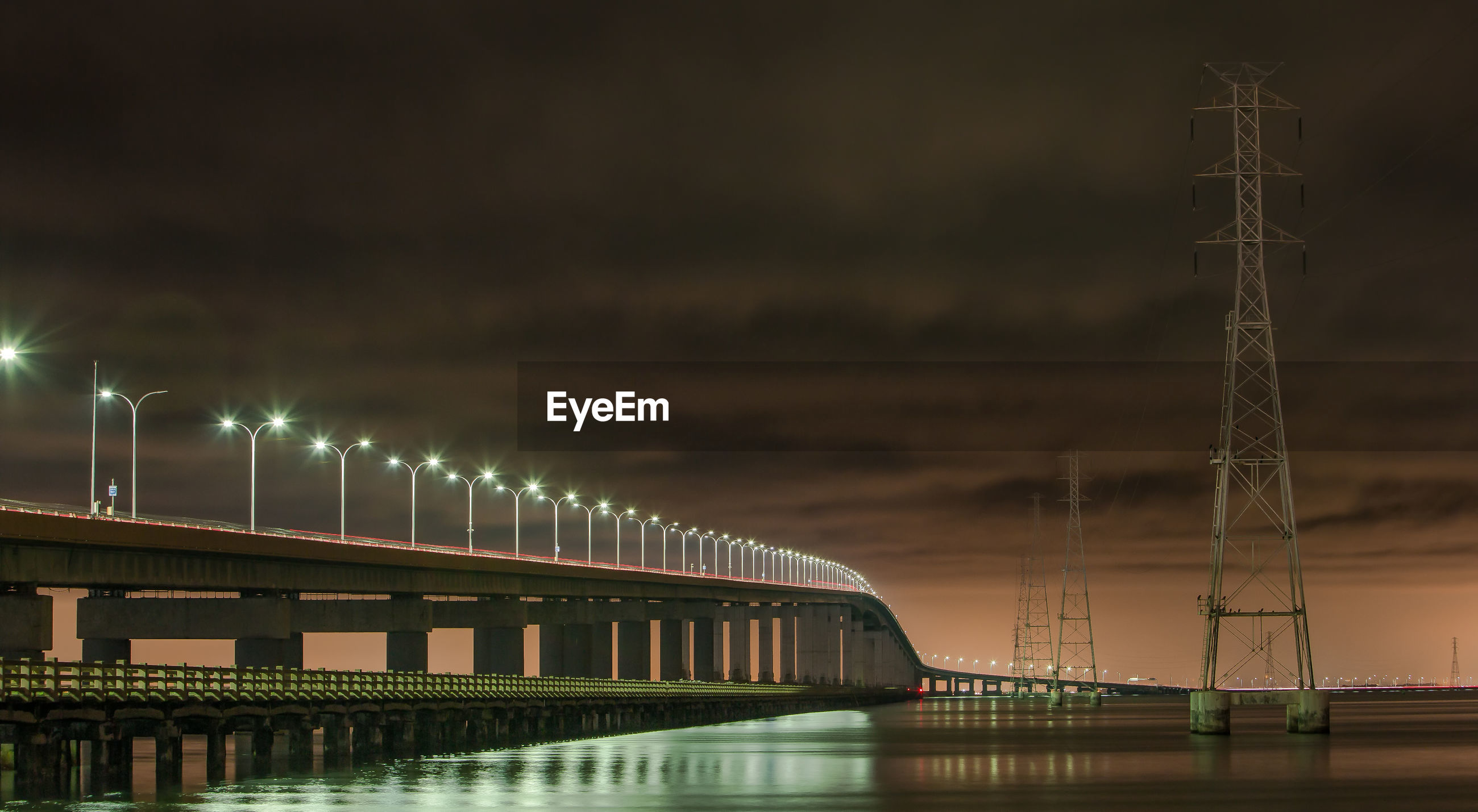 Illuminated san mateo-hayward bridge over river against cloudy sky at night