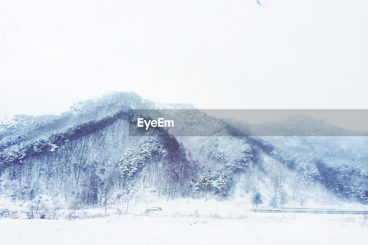 snow, winter, cold temperature, weather, nature, beauty in nature, mountain, scenics, white color, outdoors, frozen, tranquility, day, no people, clear sky, tranquil scene, mountain range, landscape, snowcapped mountain, snowing, tree, snowdrift, sky