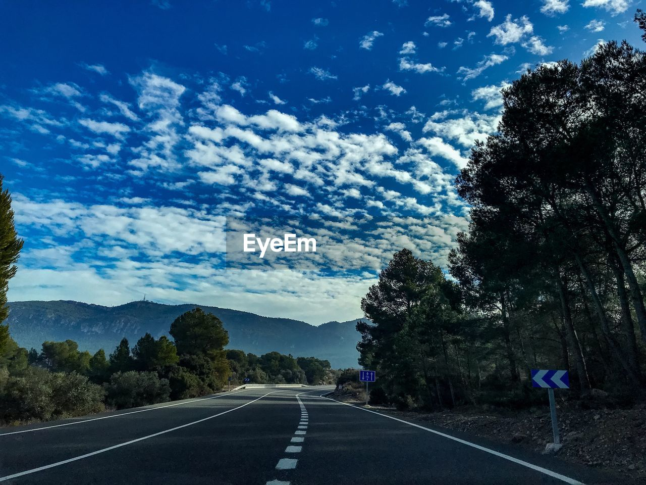 transportation, sky, road, direction, sign, the way forward, tree, symbol, cloud - sky, marking, road marking, plant, nature, mountain, diminishing perspective, day, beauty in nature, tranquility, tranquil scene, outdoors, no people, dividing line, long