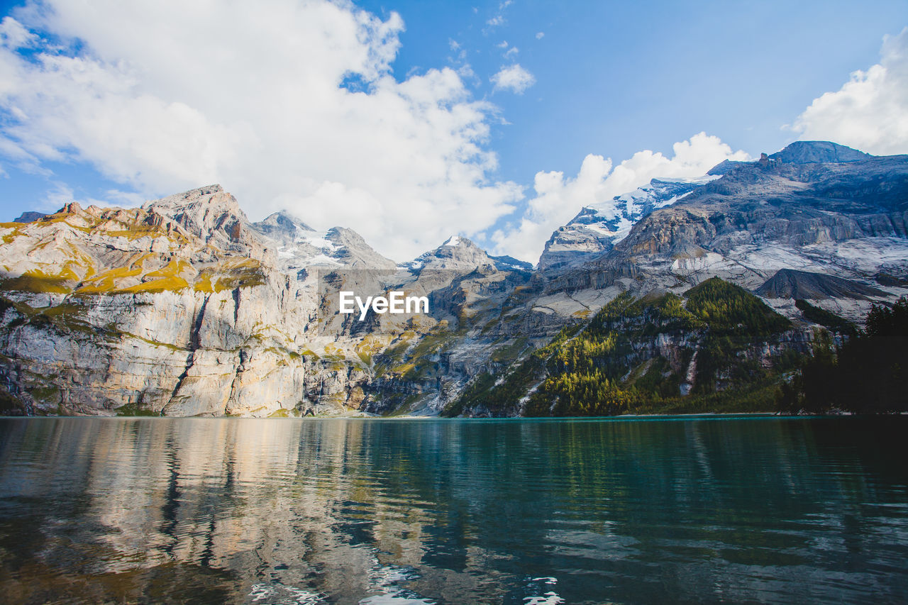 mountain, water, beauty in nature, sky, scenics - nature, tranquility, tranquil scene, lake, cloud - sky, non-urban scene, nature, idyllic, environment, cold temperature, waterfront, landscape, mountain range, reflection, day, no people, outdoors, snowcapped mountain, mountain peak, formation