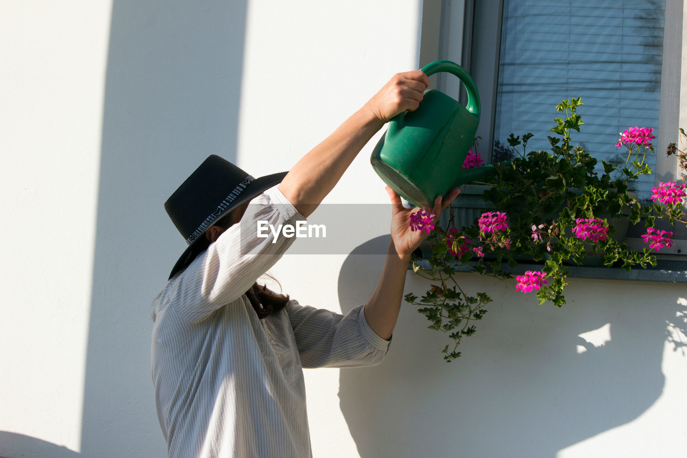 WOMAN STANDING BY FLOWER POT AGAINST WALL
