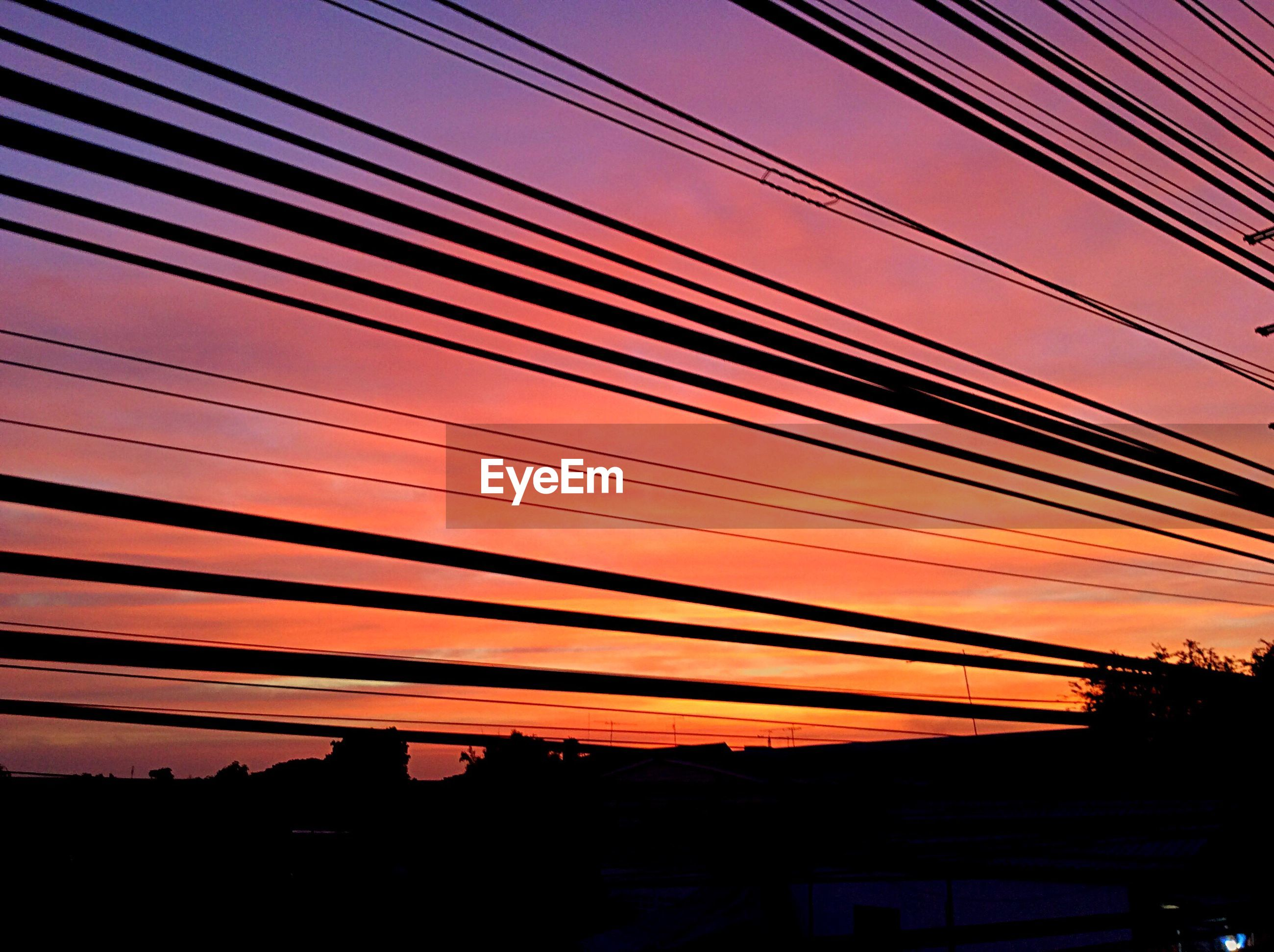 Low angle view of silhouette power lines against dramatic sky during sunset