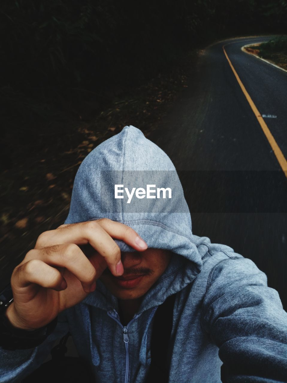 one person, front view, real people, lifestyles, casual clothing, men, holding, leisure activity, hand, portrait, hood, human hand, obscured face, transportation, clothing, day, high angle view, communication, covering, hood - clothing, finger