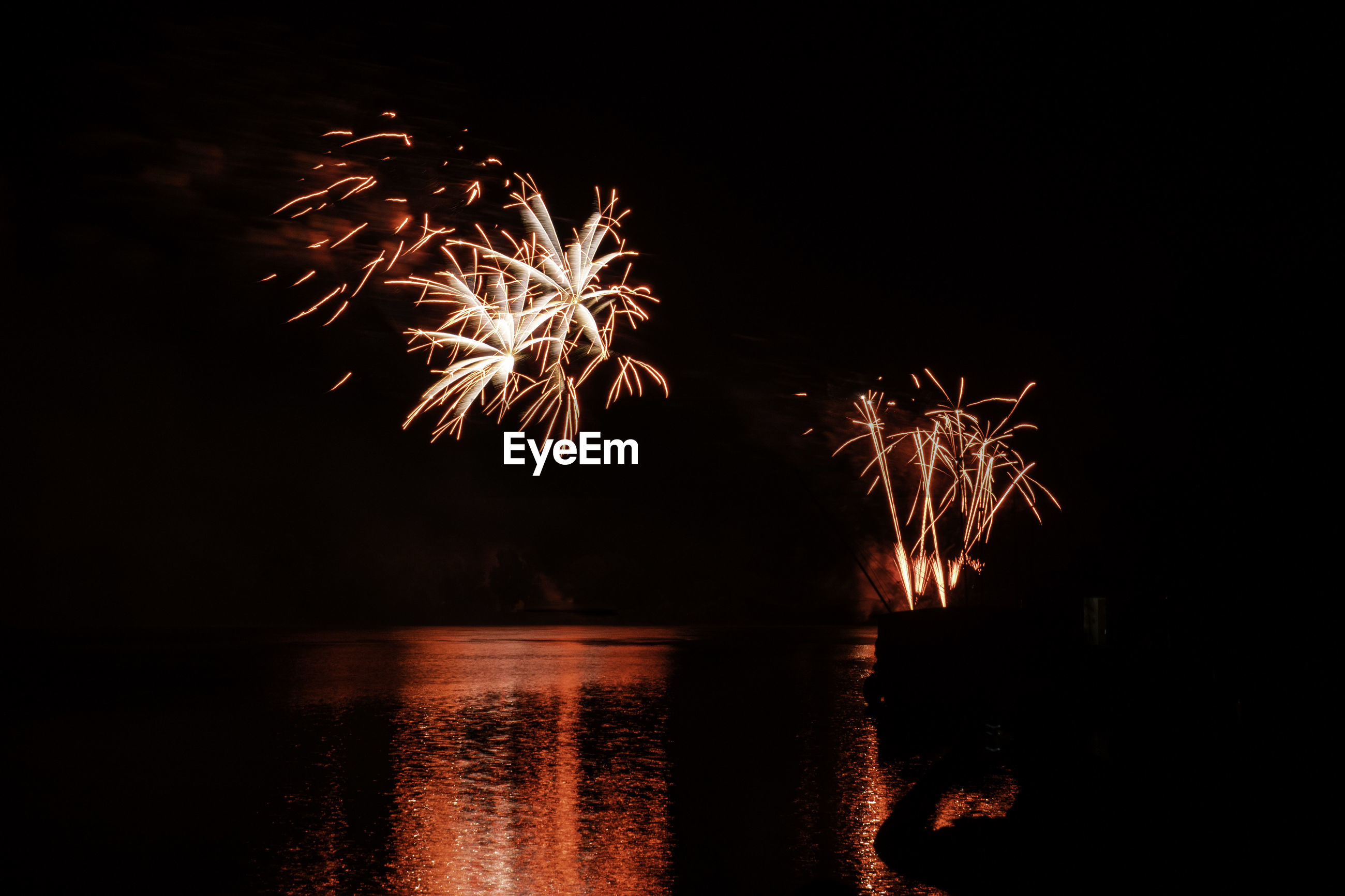 Low angle view of firework display over sea at night
