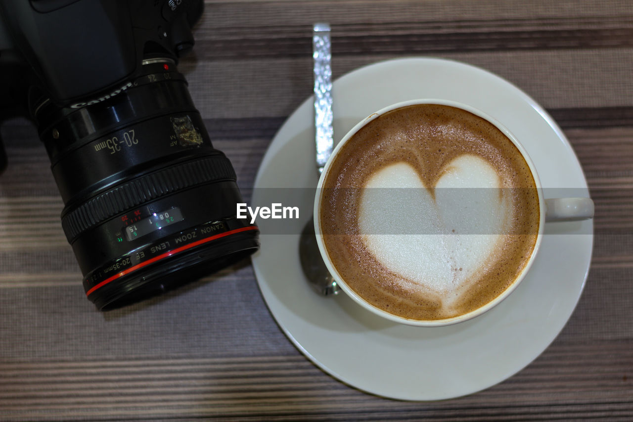 drink, refreshment, food and drink, coffee, coffee - drink, table, coffee cup, mug, cup, still life, frothy drink, indoors, freshness, hot drink, high angle view, saucer, no people, wood - material, technology, cappuccino, crockery, digital camera