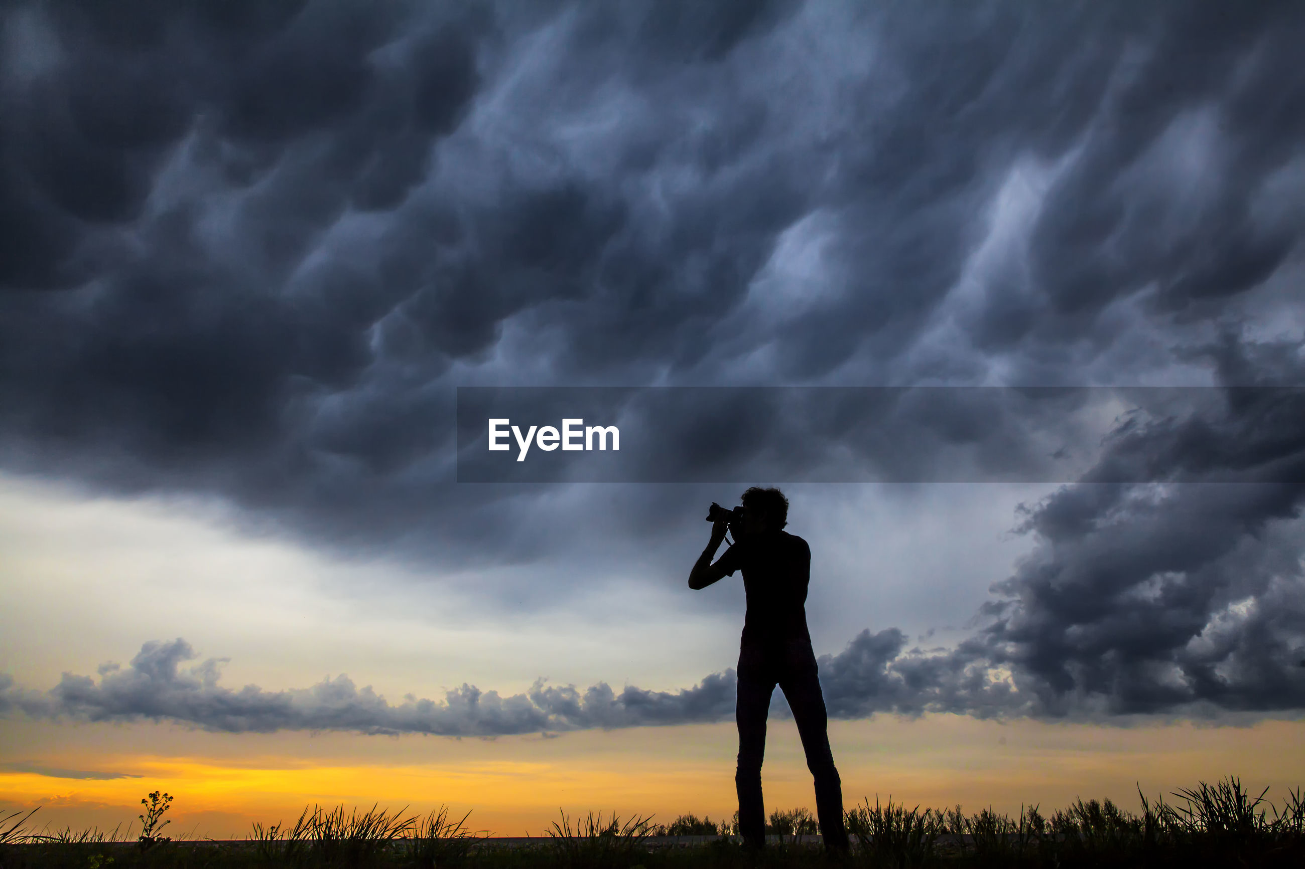 Silhouette man on field against storm clouds during sunset