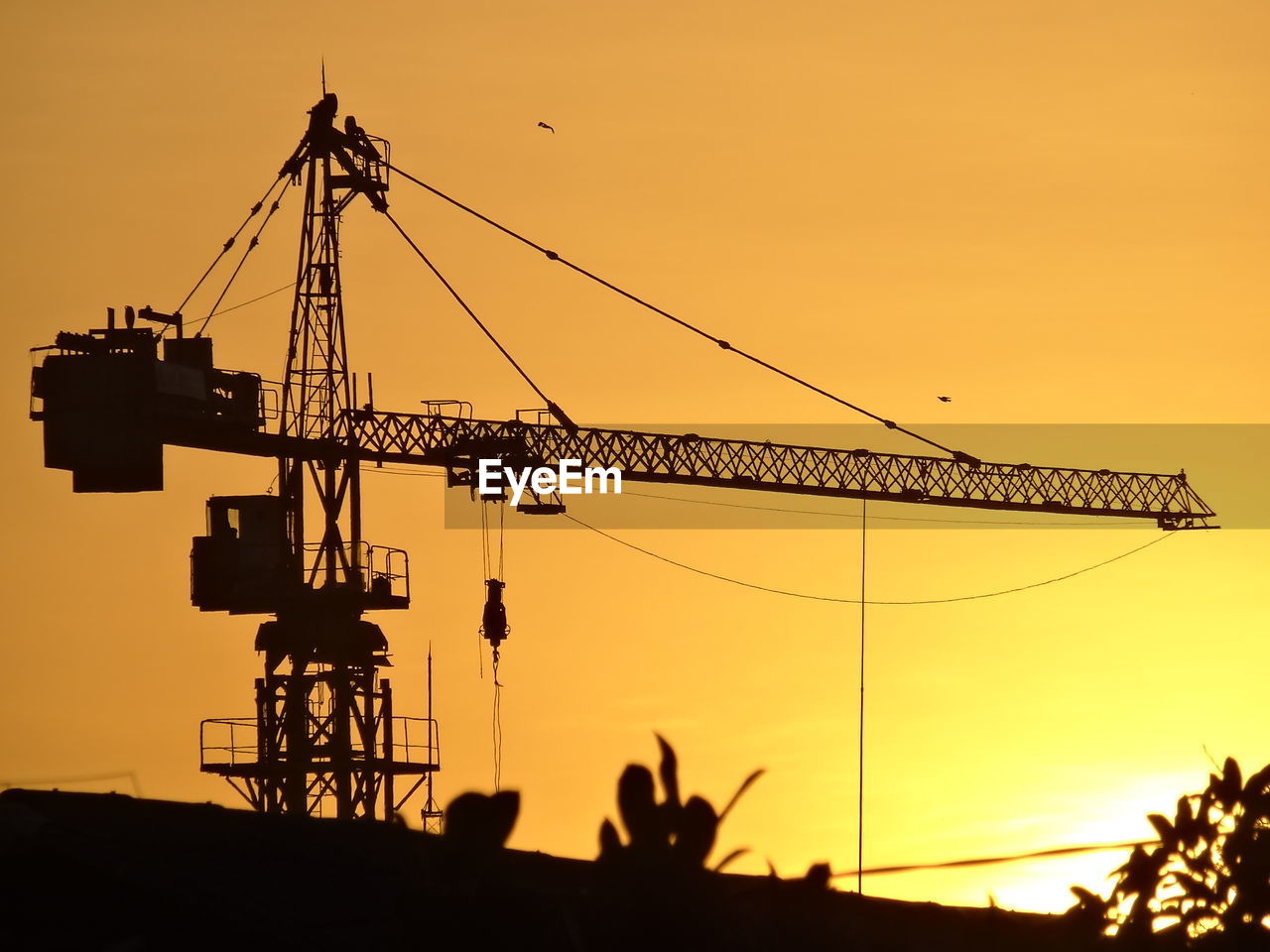 Low Angle View Of Silhouette Crane On Hill Against Clear Sky During Sunset