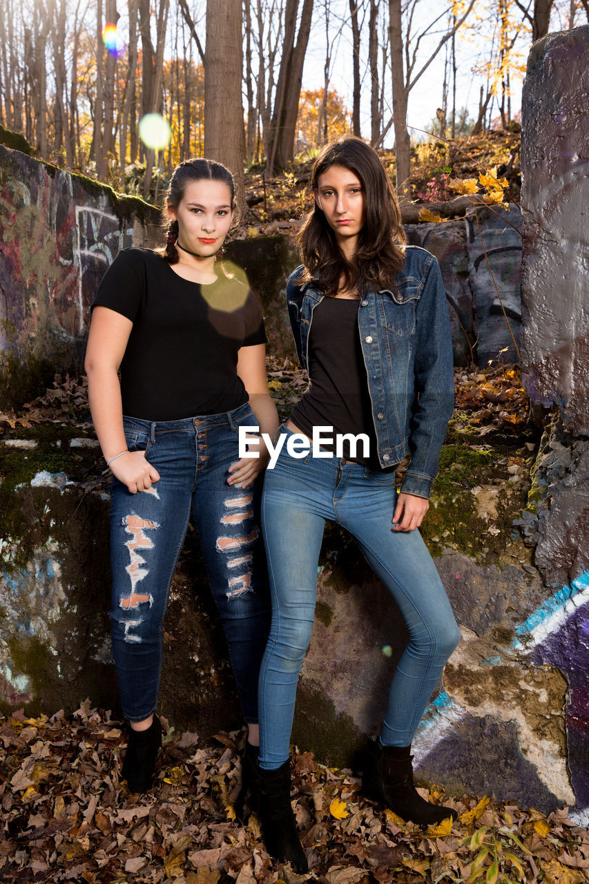 young adult, full length, two people, casual clothing, looking at camera, portrait, front view, young women, real people, standing, togetherness, bonding, lifestyles, emotion, people, tree, nature, day, women, teenager, hairstyle, outdoors, beautiful woman, jeans