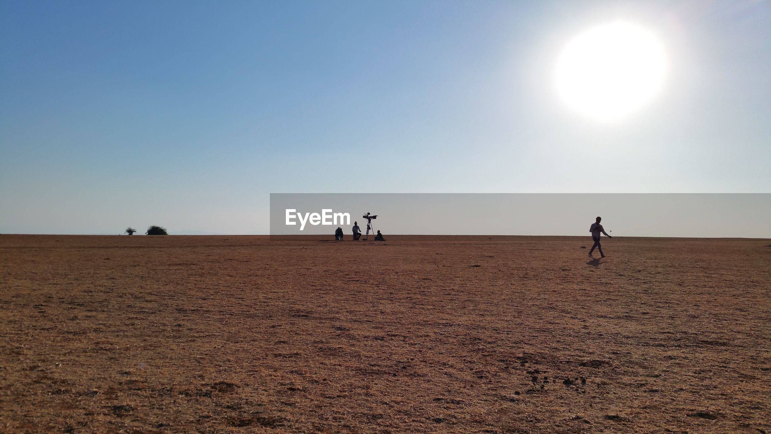 People on desert against sky during sunny day