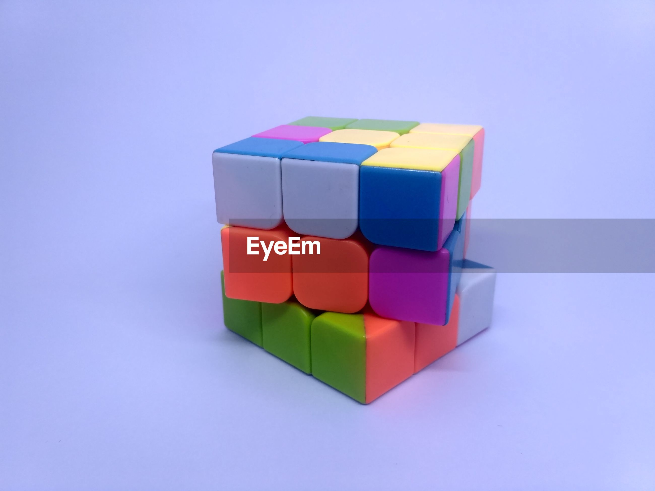 Close-up of multi colored puzzle cube over blue background