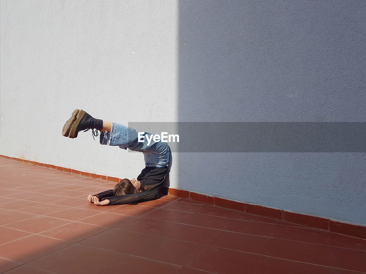 Full length of young woman stretching by wall on floor