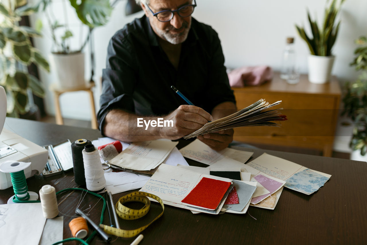 MIDSECTION OF MAN HOLDING PAPER WHILE SITTING BY TABLE