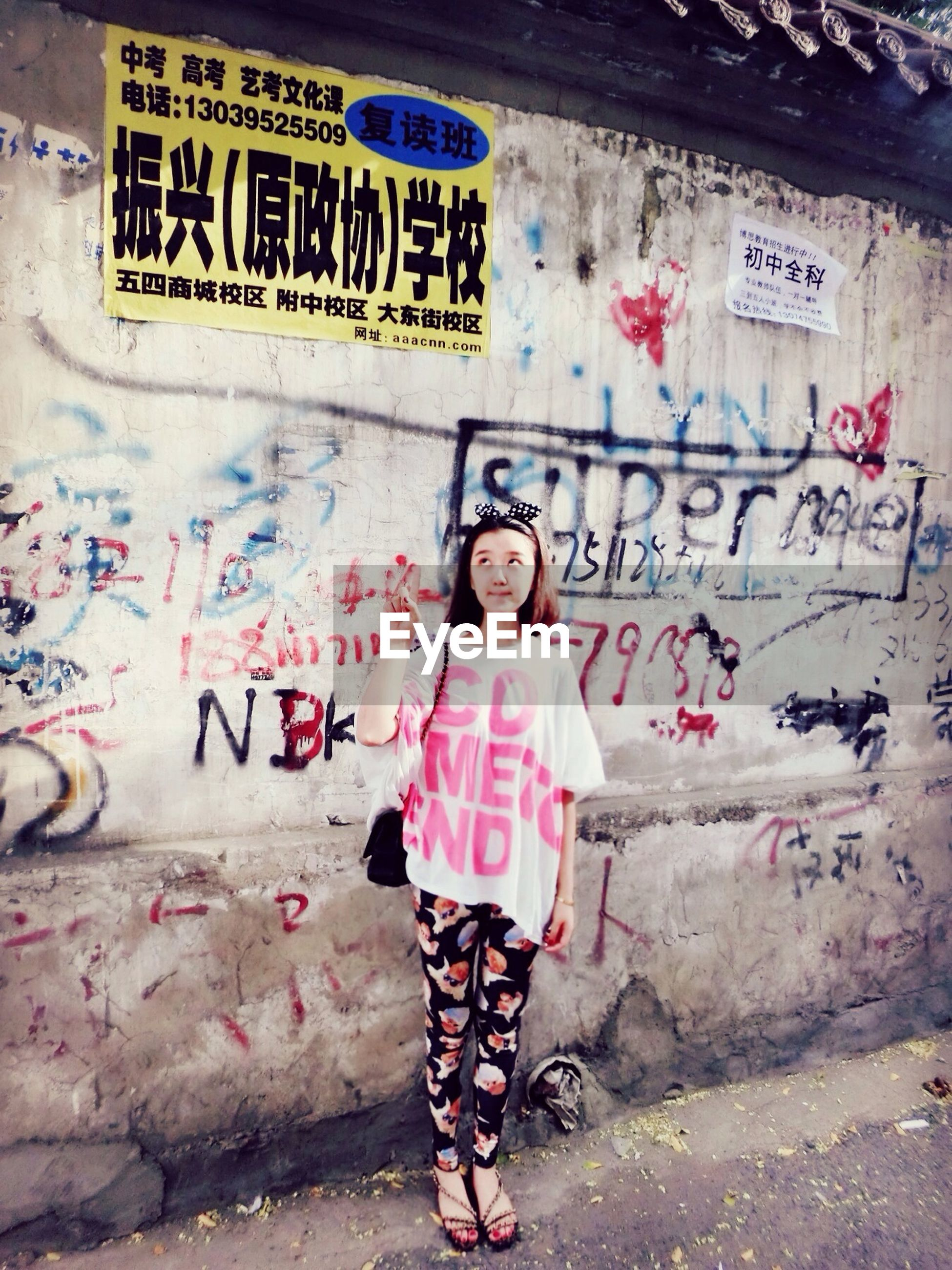 graffiti, text, western script, wall - building feature, communication, art, lifestyles, casual clothing, front view, full length, person, young adult, creativity, non-western script, standing, art and craft, street art, built structure