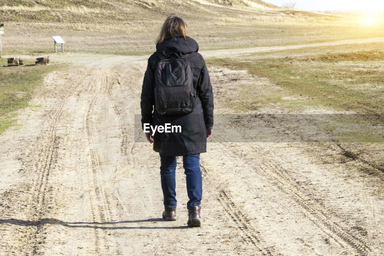 rear view, full length, one person, walking, casual clothing, adult, nature, road, young adult, backpack, clothing, day, women, land, jeans, environment, standing, landscape, outdoors