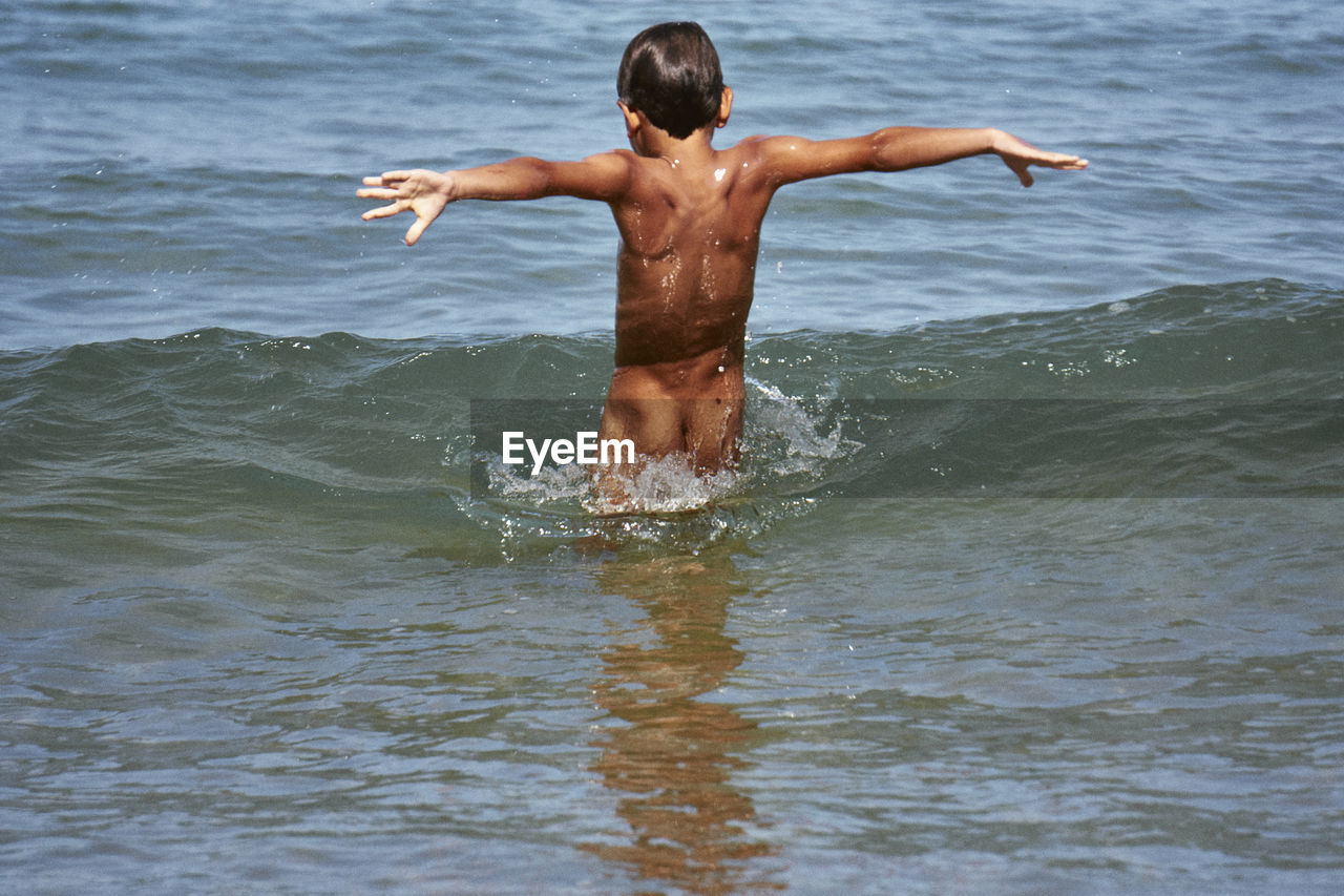 Rear View Of Naked Boy Standing In Sea