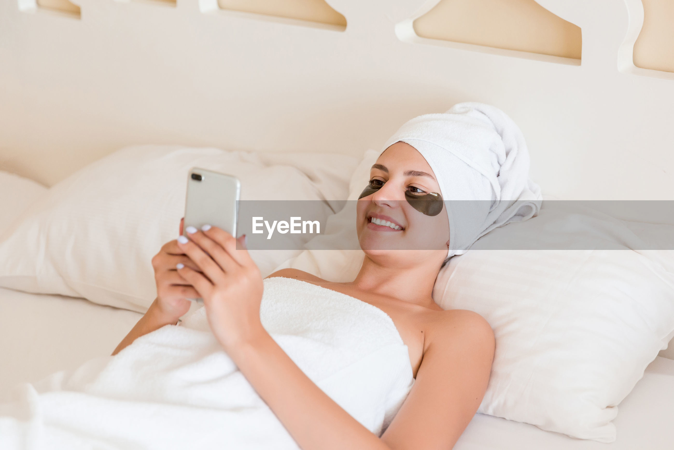 Smiling young woman with under eye patches using mobile phone on bed at spa