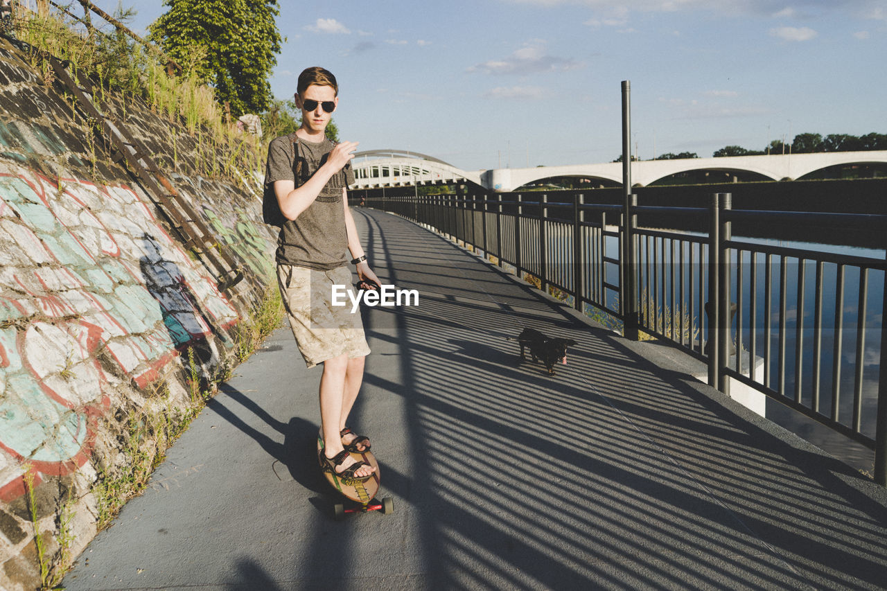 Portrait of young man skateboarding with dog