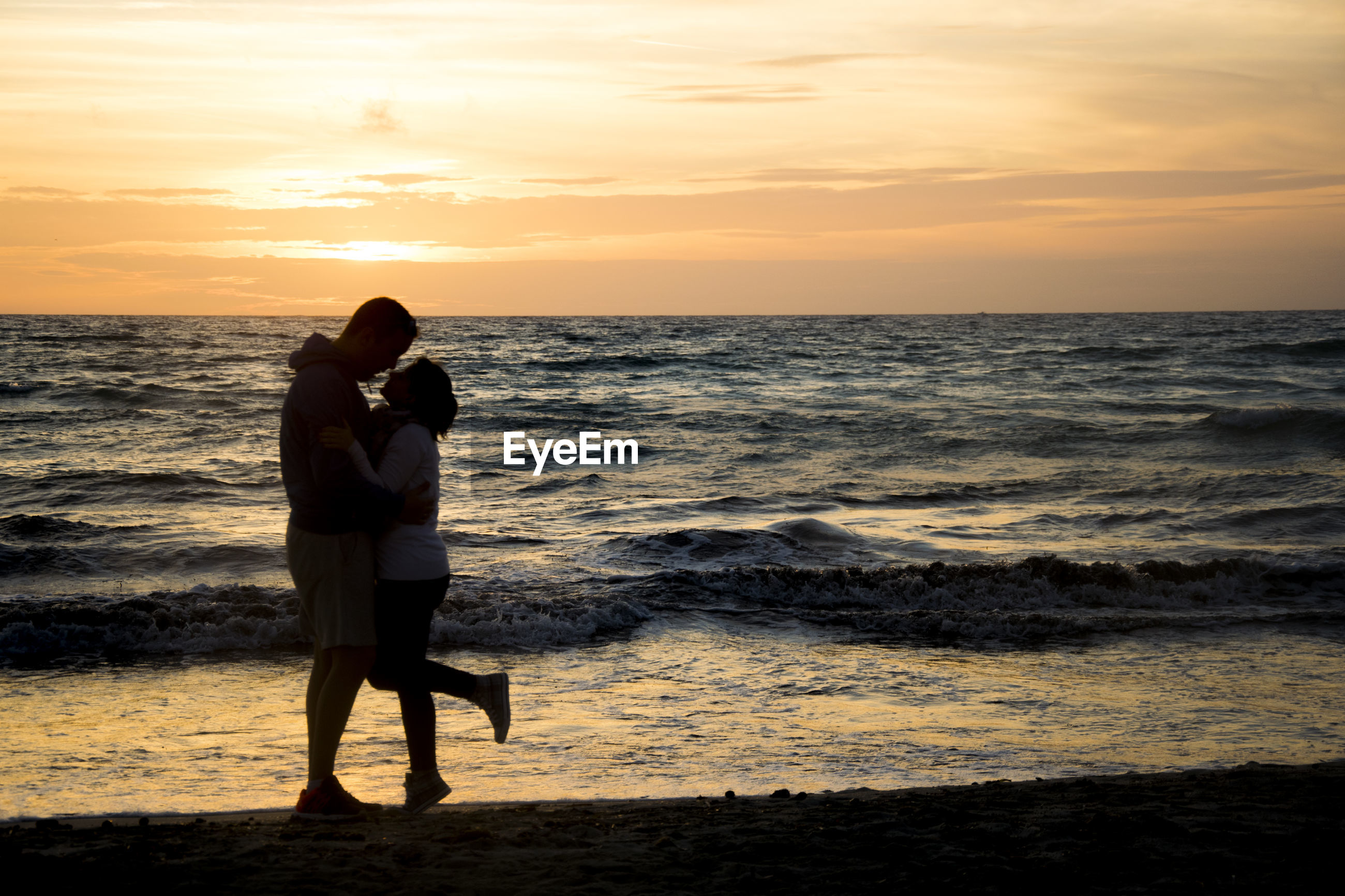 Silhouette romantic couple standing on shore at beach against sky during sunset