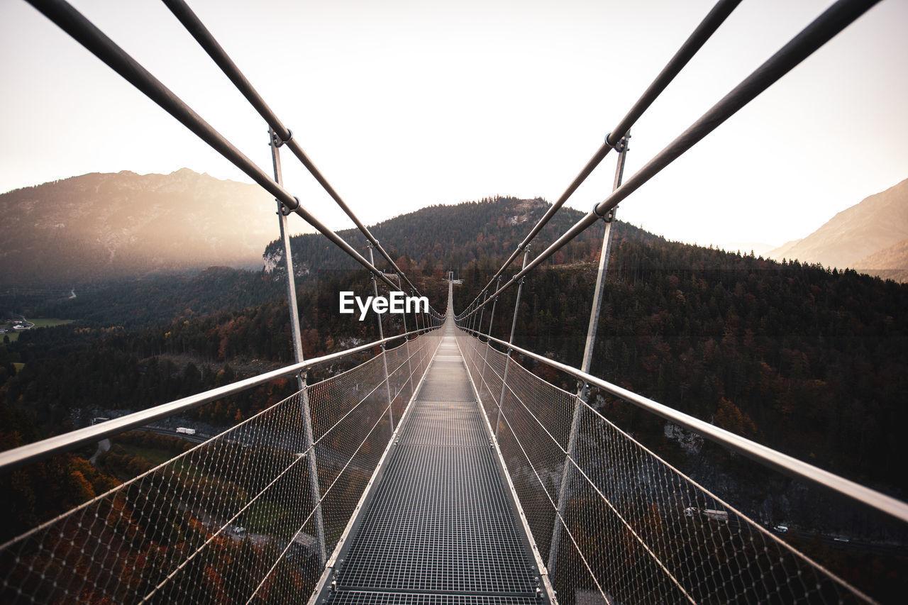 Long Empty Footbridge Against Clear Sky During Sunrise