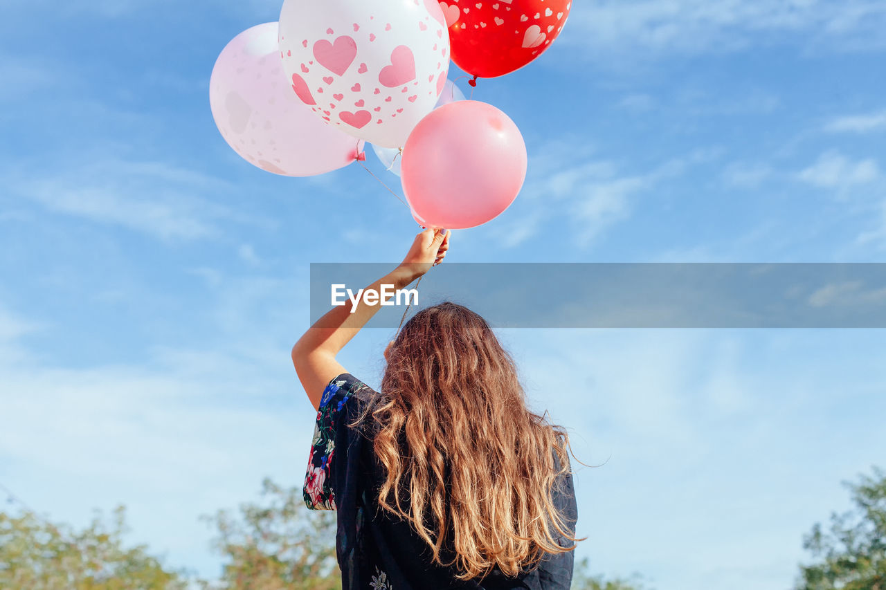 Rear View Of Woman Holding Helium Balloons Against Blue Sky