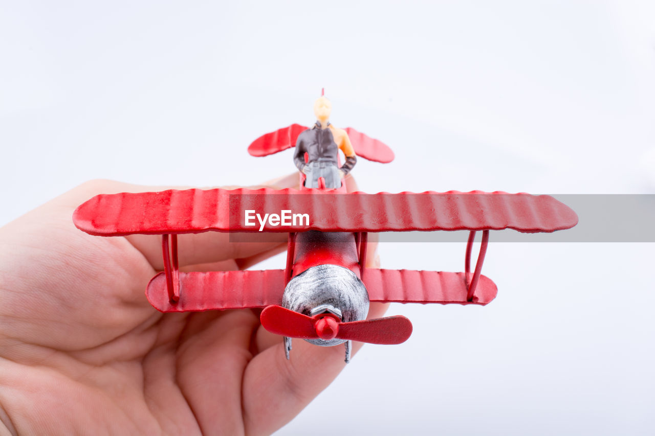 Close-up of cropped hand holding red model airplane with figurine against white background