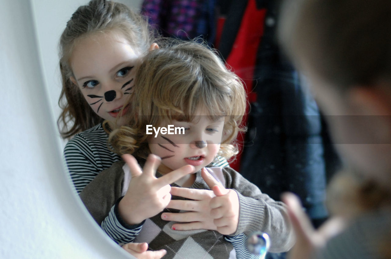 Cute sisters with face paint gesturing on mirror at home