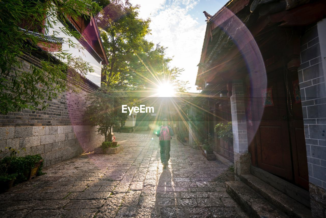 architecture, built structure, building exterior, real people, sunlight, lens flare, nature, sunbeam, plant, tree, sun, rear view, direction, day, footpath, city, lifestyles, people, the way forward, full length, outdoors, paving stone