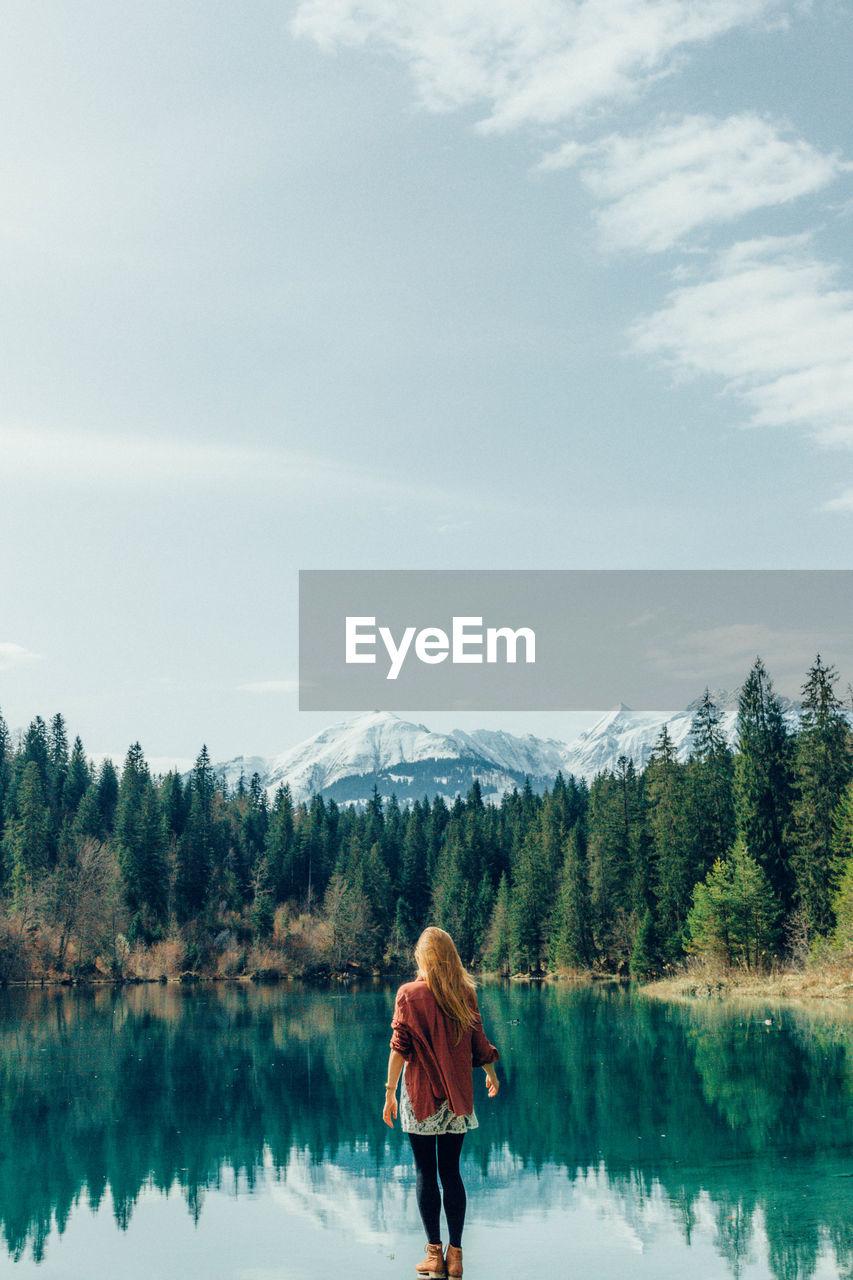 Rear view of woman standing by idyllic lake