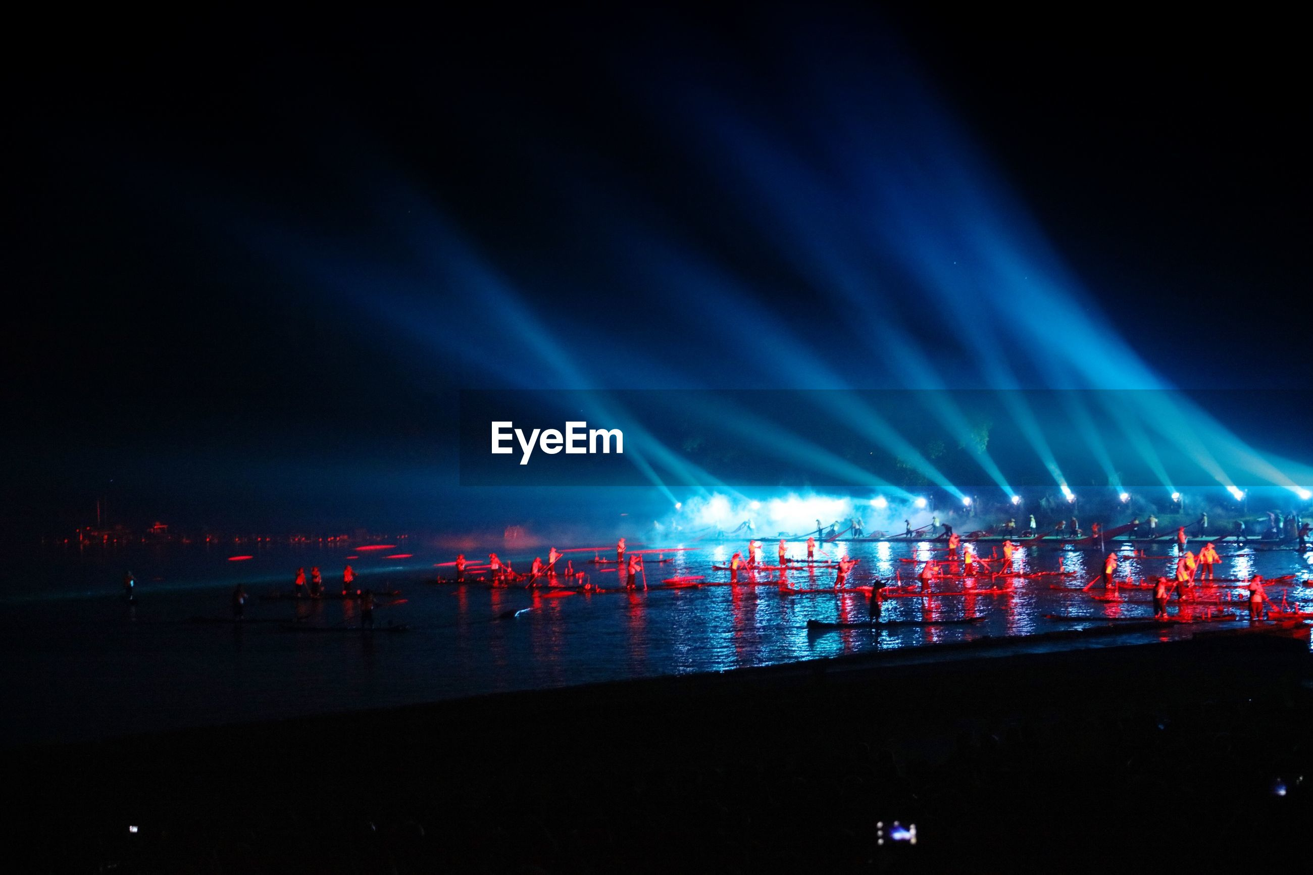 Illuminated red boats moored at river during event