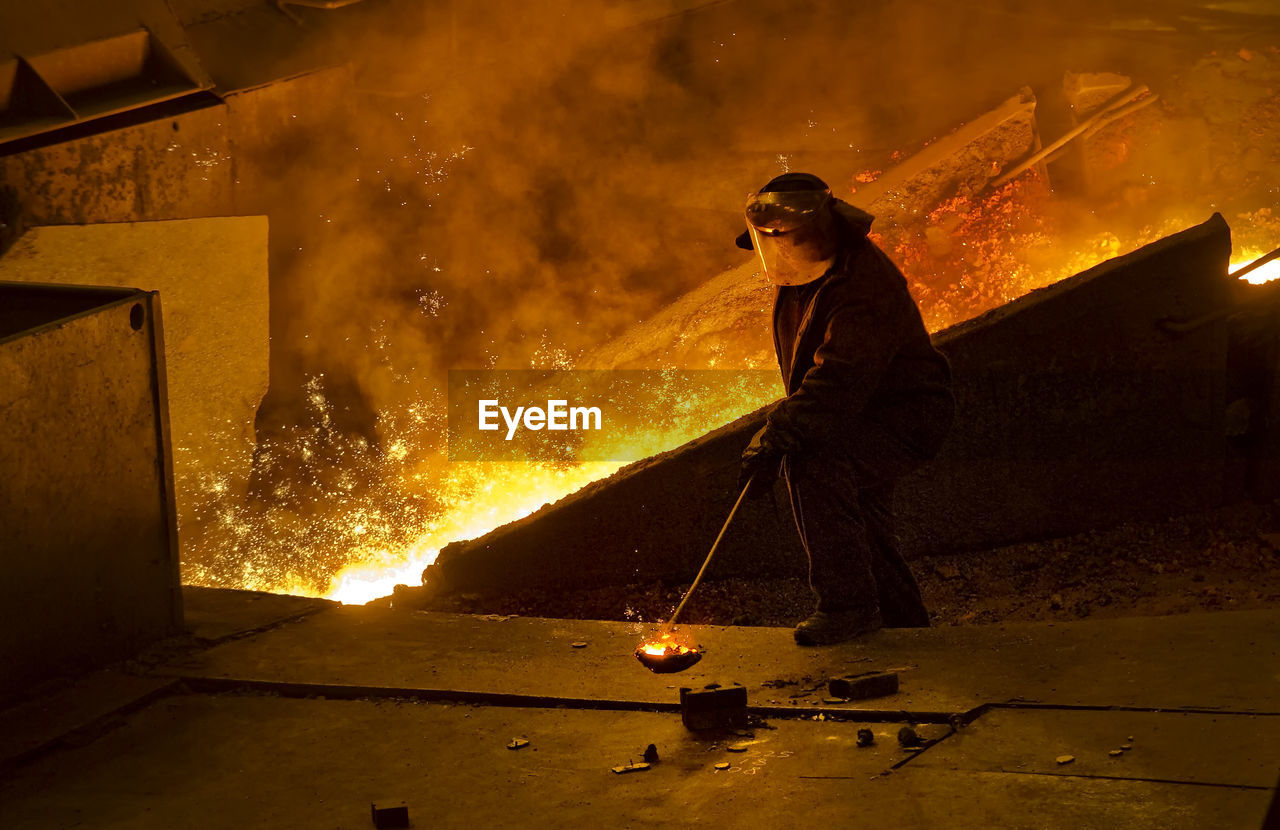 Full length of man working while standing by fire in factory
