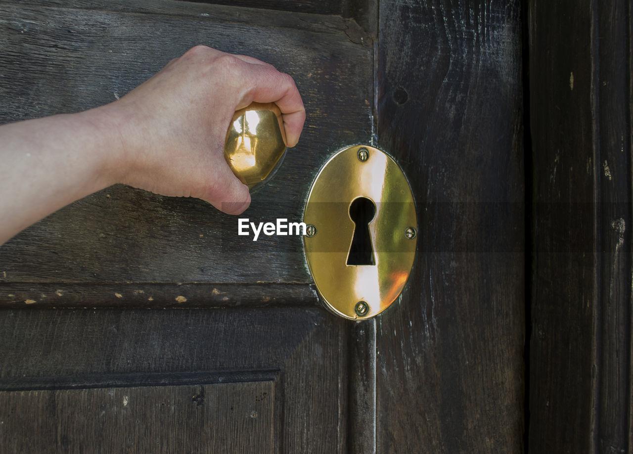 Cropped Hand Holding Golden Doorknob On Wooden Door