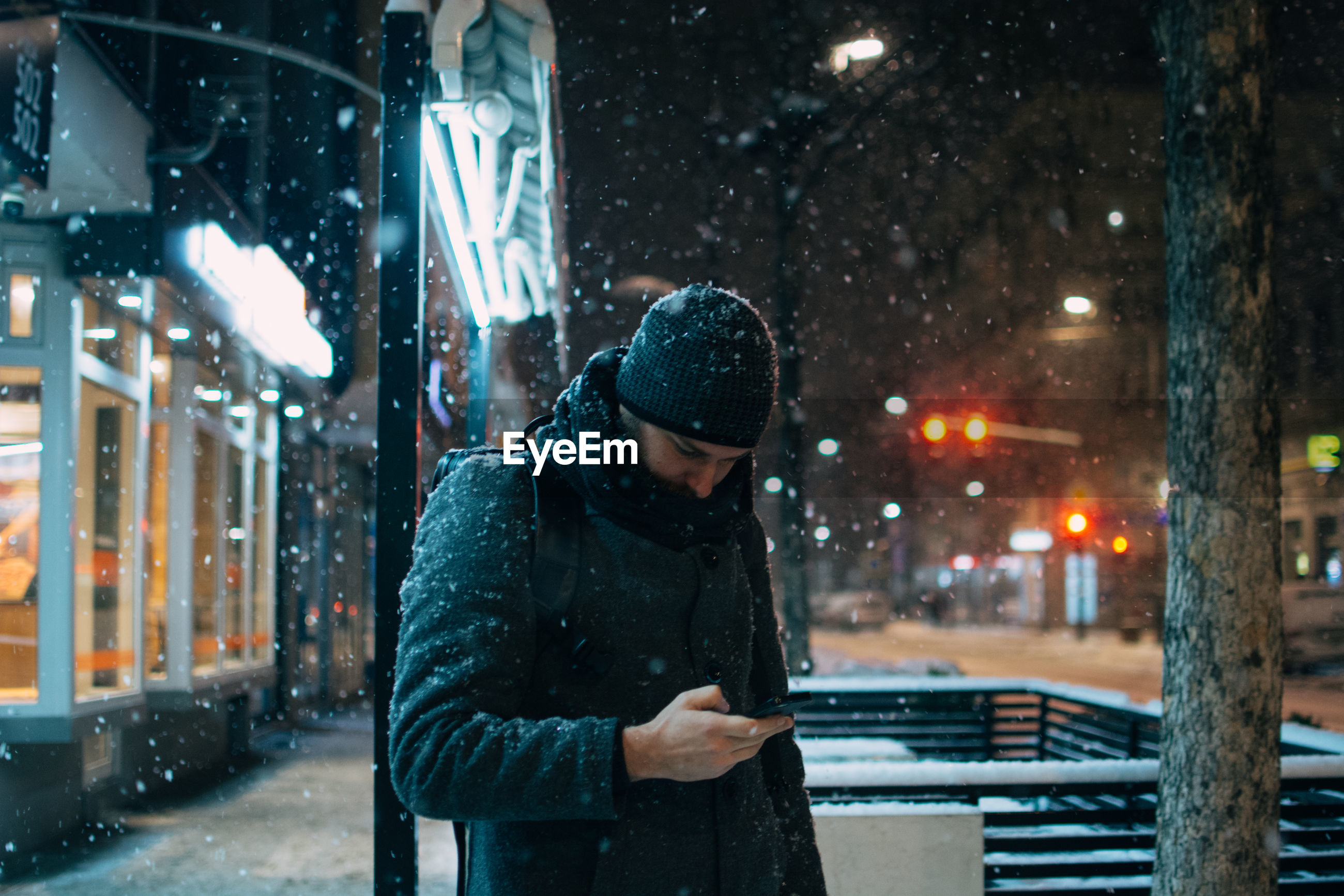 Man using phone on street in city at night during winter