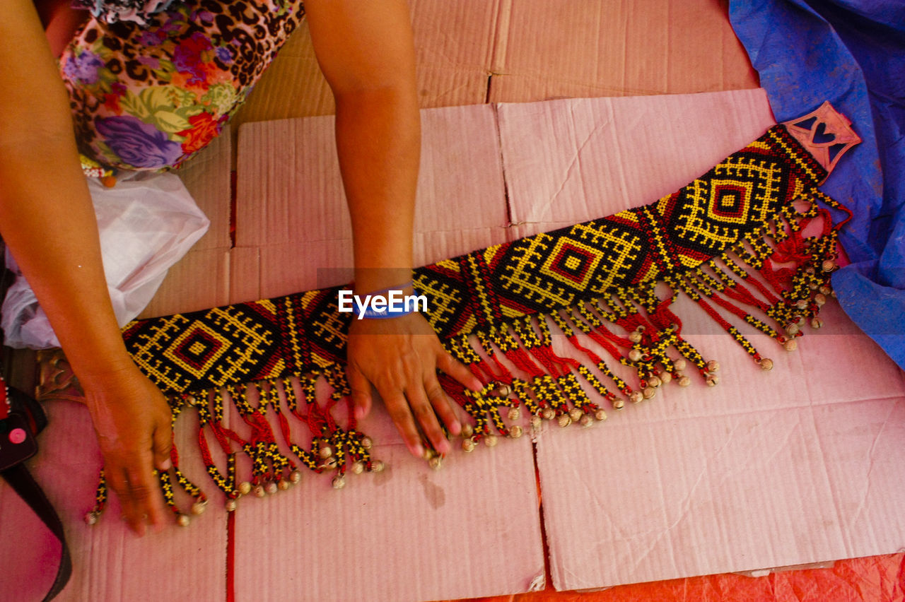 Cropped hands of woman touching beaded fabric