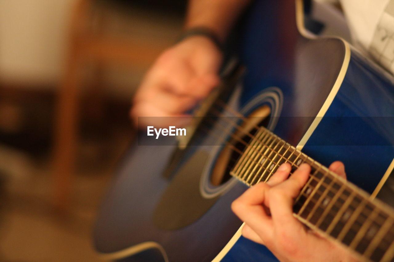 Cropped image of man plucking guitar