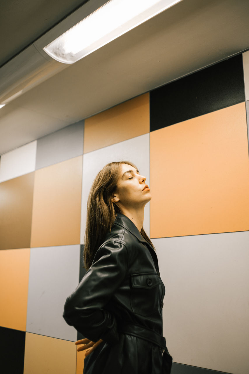 Young woman standing by wall at subway station