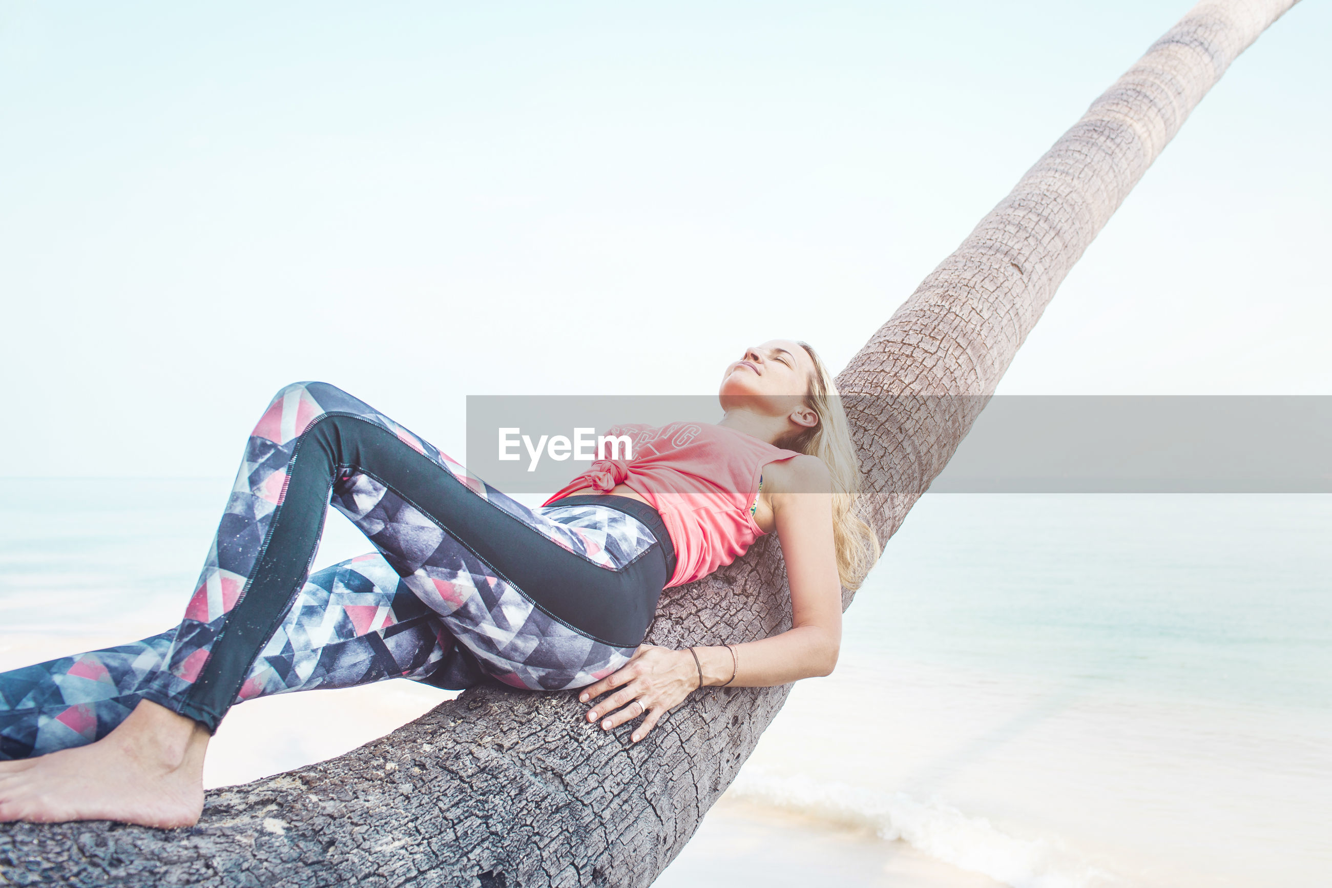 Woman lying on coconut palm tree at beach during summer